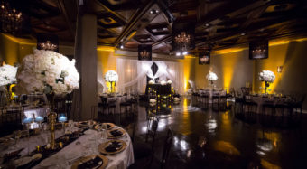 wedding reception setup with white centerpieces and gold lighting in the ella banquet hall at noor pasadena