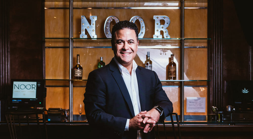 robert shahnazarian noor los angeles general manager leaning on the bar of the ella banquet hall