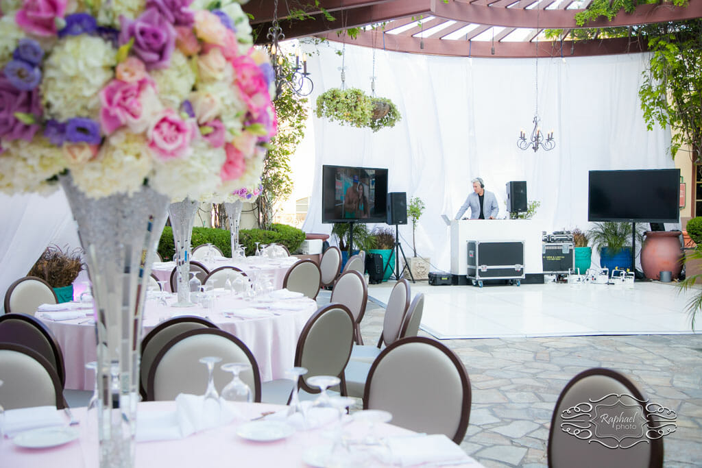 outdoor party setup with dj, flowers and tables