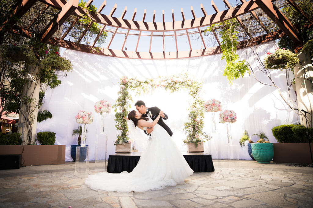 outdoor wedding ceremony bride and groom kiss in front of a floral arch