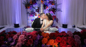bride and groom seated at sweetheart table surrounded by red orange and pink flowers and a wedding cake behind them