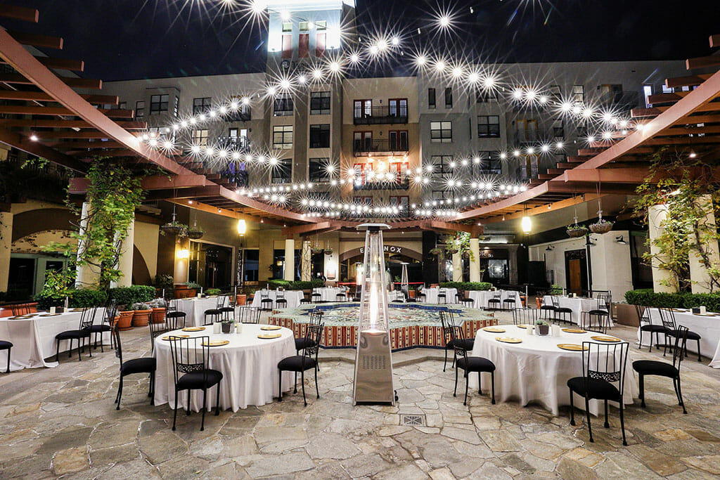 bat mitzvah venue the NOOR terrace with tables and chairs plus fountain and string lights